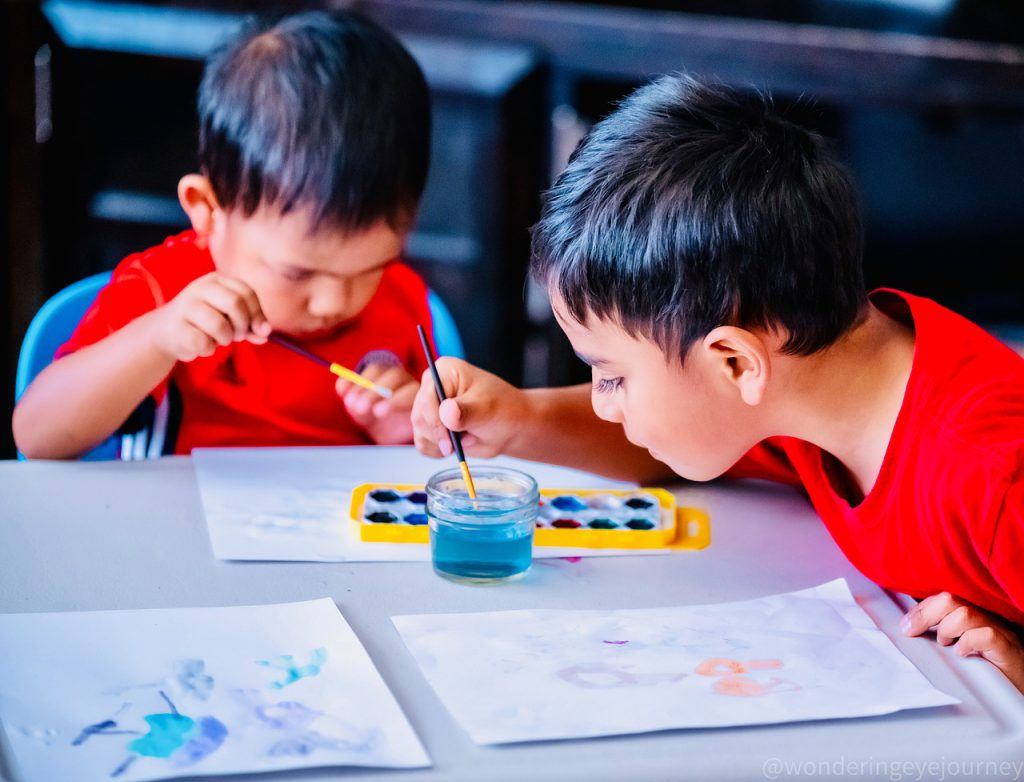 two young boys painting with watercolors