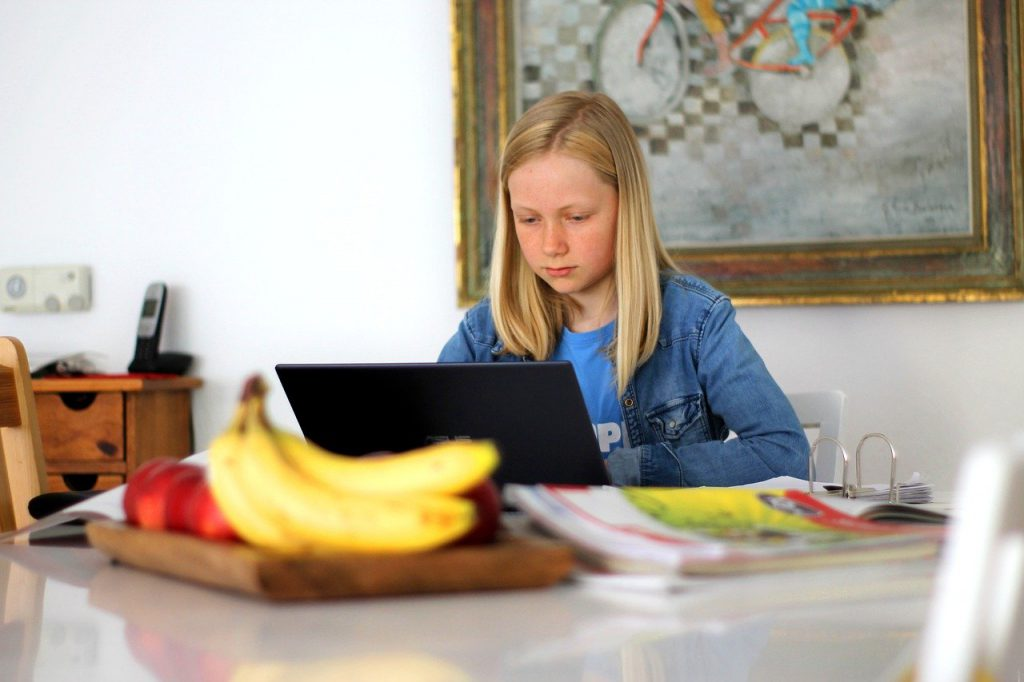 girl with laptop doing schoolwork